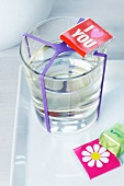 Chocolates with greetings and pictures on wrappers and glass of water with purple rubber band