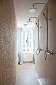 Shower heads in narrow shower area and view of window with floor-length curtains