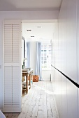 White louver door next to open doorway with view of twin sinks opposite white fitted cupboards