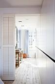 Tür mit weissen Lamellen neben offenen Durchgang und Blick auf Waschbereich gegenüber weissen Einbauschränken