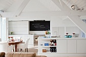 Open-plan interior with kitchen counter and dining area in renovated attic with white wood cladding