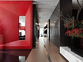 Hardwood hallway in modern building with red accent wall