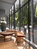 Loggia mit rustikal eleganten Holzmöbeln vor Glasfassade und Schiebeelementen aus Metallgitter