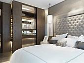 Doppelbett mit gepolstertem Kopfteil neben Ankleide mit offenen Schiebetüren im modernen Schlafzimmer