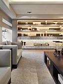 Beleuchtetes Einbauregal und helle Polstergarnitur in klassisch modernen Wohnraum