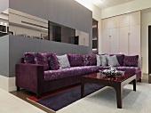 Eckcouch mit gemustertem, violetten Stoffbezug und Couchtisch vor grau getöntem Raumeinbau