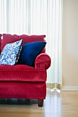 Red sofa with blue accent throw pillows