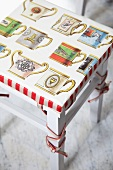 Cushion with pattern of vintage mugs on kitchen stool