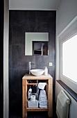 Waschtisch aus Holz mit Keramikschüssel vor grauen Wandfliesen im Designerbad