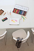 Large box of coloured pencils, watercolour paints and drawing pad on white table with upholstered designer chairs