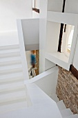 Complex, angular, white staircase with interesting perspectives and surfaces including stone walls and wooden beams - person seen through stairwell lending a sense of scale