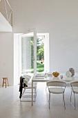 Puristischer Gemeinschaftsraum mit offener Tür in den Garten - Designerstühle aus weißem Leder und Metall an grossem Tisch. weiße Gestaltung im Kontrast zum Blick nach draußen ins Grüne.