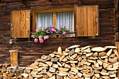 Firewood stacked against outside wall of log cabin with window box below window