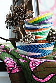 Hand-woven baskets of colourful wire in front of vase with floral relief elements on African fabric