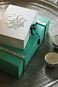 White and green painted wooden boxes ornamented with metal details on Oriental metal tray