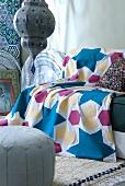 Gemusterte Tagesdecke auf Sofa und Ledersitzpolster vor tief hängender Deckenleuchte in orientalischem Stil