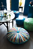 Pouffes with different covers next to side table holding Oriental-style metal tray