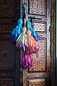 Colourful cord tassels on handle of Oriental-style cabinet door
