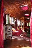 Blick in alten Zirkuswagen auf Vintage Küchenherd neben Polstersofa in gemütlichem holzverkleidetem Innenraum