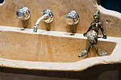 Old stone sink with wall-mounted taps and brass figurine of a woman
