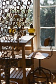 Curtain of linked bast-fibre rings in front of plain desk in front of window