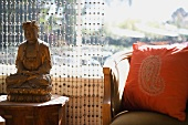 Wooden Buddha figurine in front of bead curtain and ethnic cushion on armchair