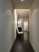 Upholstered chair next to chest of drawers in narrow corridor with recessed spotlights