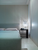 Modern bedroom with double bed next to bedside table with lamp