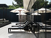 Contemporary outdoor furniture with parasol on tiled terrace against glass facade of apartment building