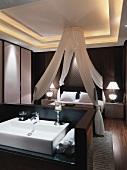 Blick über Waschtisch auf Himmelbett mit Baldachin in klassisch, modernem Schlafzimmer