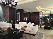 Sofa set with light upholstery in front of dining area with indirect ceiling lighting in classic, modern interior