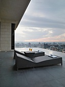 Modern outdoor loungers on roof terrace with view over cityscape