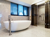 Free-standing bathtub in front of floor-level shower area with sliding glass door in marble-clad bathroom