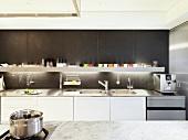 Designer kitchen with white kitchen units and backlit shelf against dark-grey wall