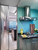 Kitchen counter with stainless steel extractor hood next to half-open glass door with view into room beyond