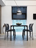 Black table with chairs in front of window in white dining room