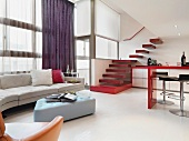 Designer interior furnishings and counter with barstools in open-plan kitchen below stairs leading to gallery