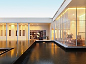 Contemporary building with pool in courtyard and view into illuminated rooms