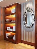 Illuminated, fitted shelving next to mirror with ornate silver frame on wall with striped wallpaper