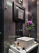 Marble basin on washstand against wall with mosaic tiles in iridescent shades of purple