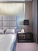 Corner of bedroom - bedclothes and upholstered headboard of double bed in matching, shimmering fabric