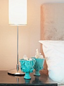 Decorative, turquoise goblets and table lamps on bedside table