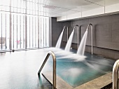 Cascade showers spouting into indoor pool in contemporary building