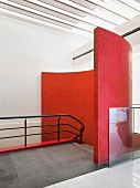 Open-plan stairwell with curved, red wall and light strips on ceiling