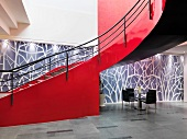 Curved staircase with red stringer walls against artistic wall in spacious foyer