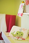 Detail of Baby's Changing Table with Whale Towel and Shoes