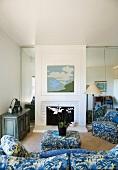 Wohnzimmer mit Kamin und blau gemusterter Polstergarnitur
