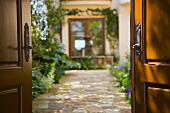 Stone path leading into Spanish style courtyard with fountain.