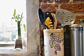 Detail of kitchen utensils next to window.