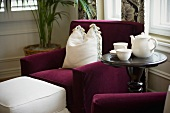 Vignette of purple chair with white pillow and tea set